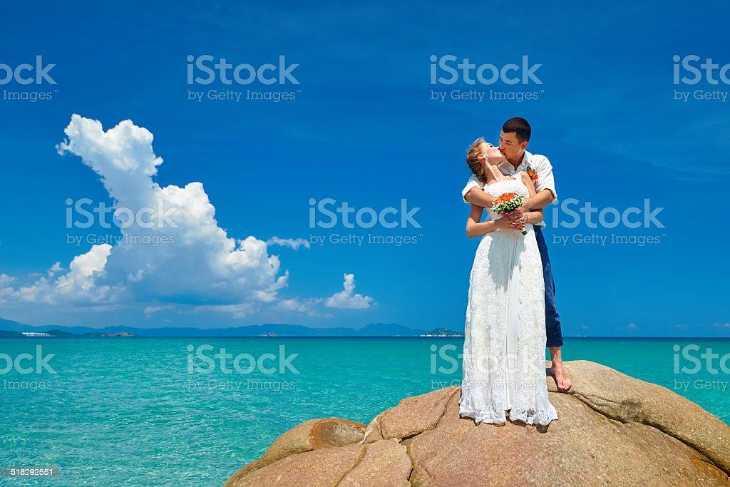 Noivo e noiva em pé com buquê de flores no mar praia - foto de acervo
