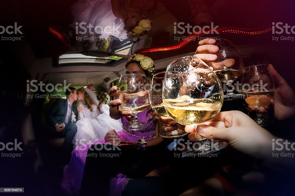 groom and  bride with friends are in the wedding car stock photo
