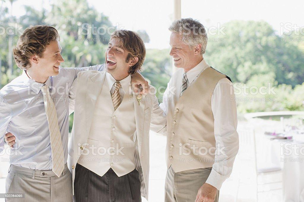 Groom and groomsmen hugging stock photo