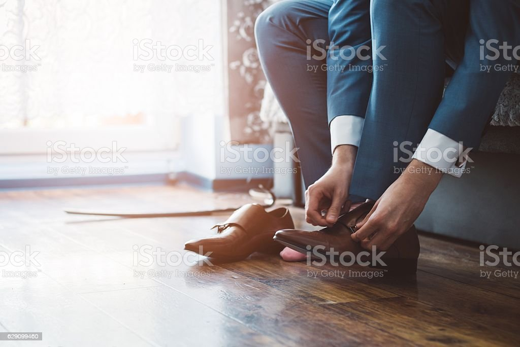 Groom dressing up with classic elegant shoes. stock photo