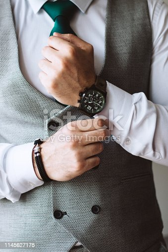 Groom fixing cuff links on his shirt, wearing luxury clothes and expensive wristwatch