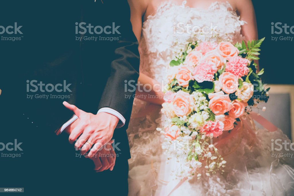 groom hand with bouquet of flowers in bride hand royalty-free stock photo