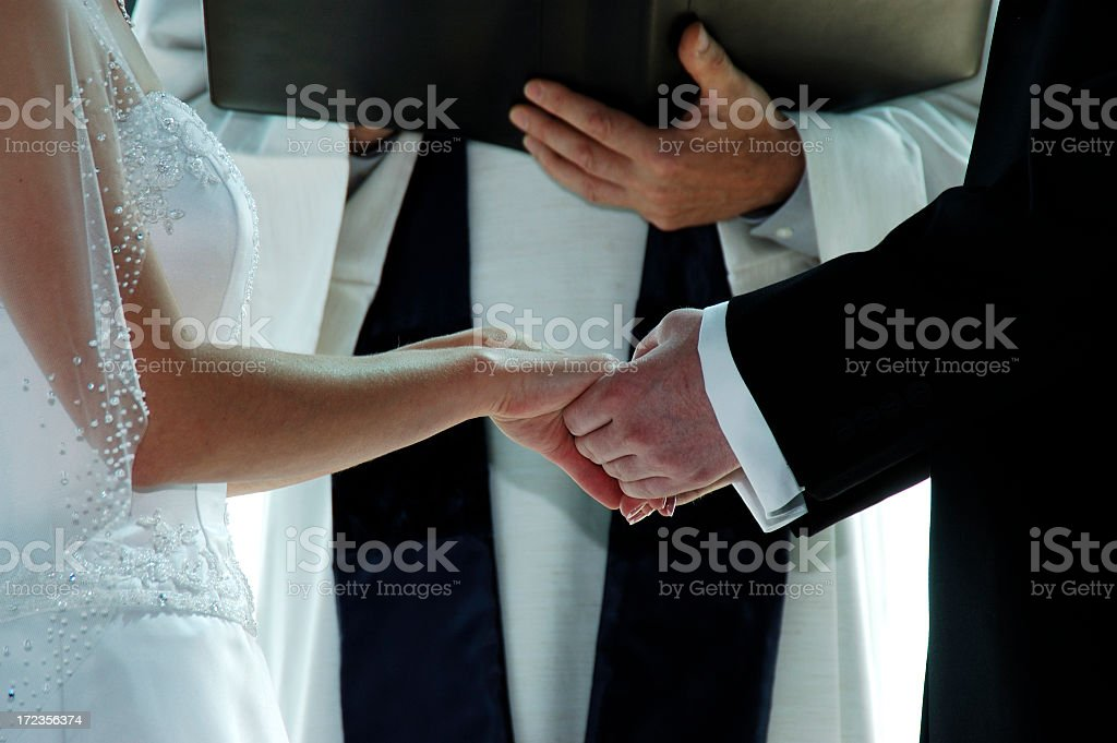 Groom holding a bride's hands on their wedding day royalty-free stock photo