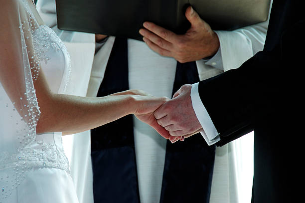 Groom holding a bride's hands on their wedding day stock photo