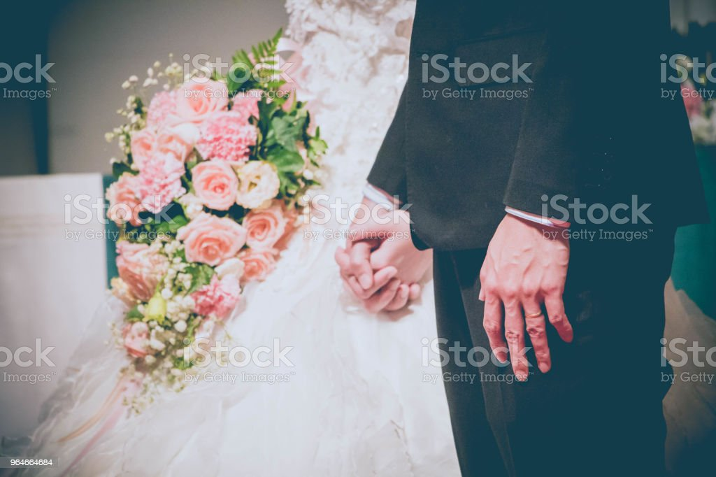 groom holding bride hand with bouquet of flowers royalty-free stock photo