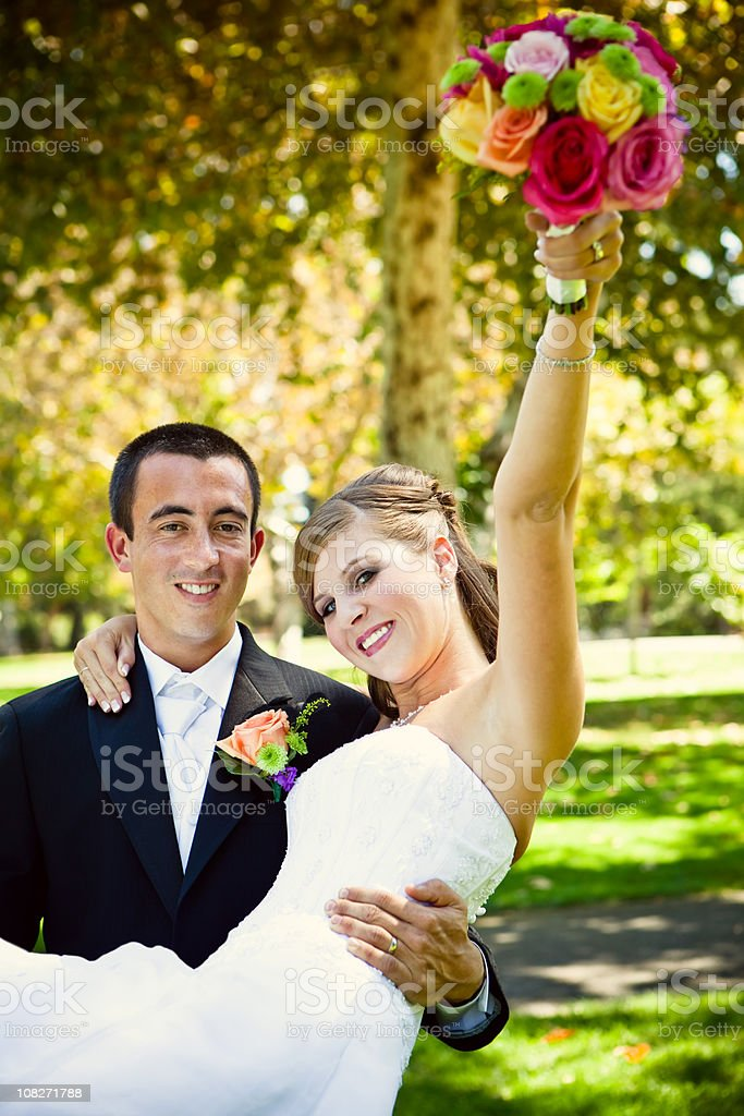 groom holding bride with bouquet in air royalty-free stock photo