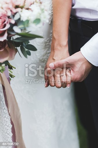 istock Groom holding bride's hand with a ring 637338732