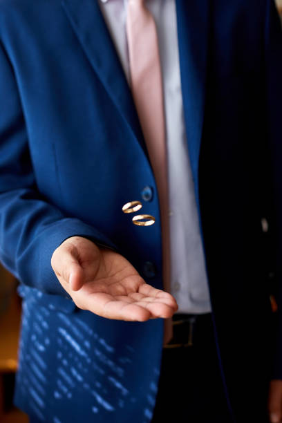 Bräutigam hält Eheringe auf der Handfläche, Ehering in Derpflegehand. Ein Mann wirft die Ringe hoch. – Foto