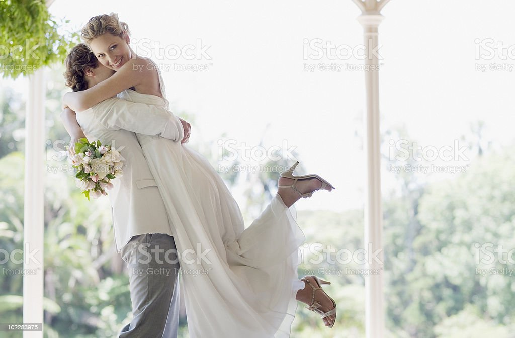 Groom hugging and lifting bride stock photo