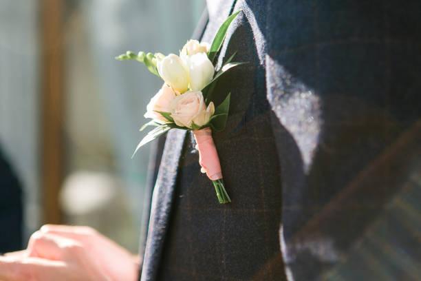 bräutigam in dunklen grauen anzug mit einem weißen rose boutonniere. schuss in sonnenstrahlen hautnah - bräutigam anzug vintage stock-fotos und bilder