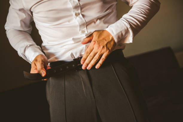 Groom in gray pants and a white shirt fastens his leather belt. stock photo