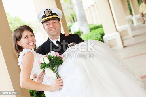 674214372istockphoto Groom in Navy Uniform Holding His New Bride 183811229