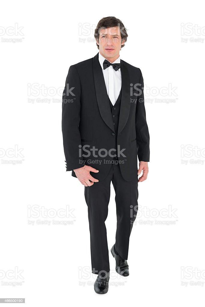 Groom in tuxedo walking over white background stock photo