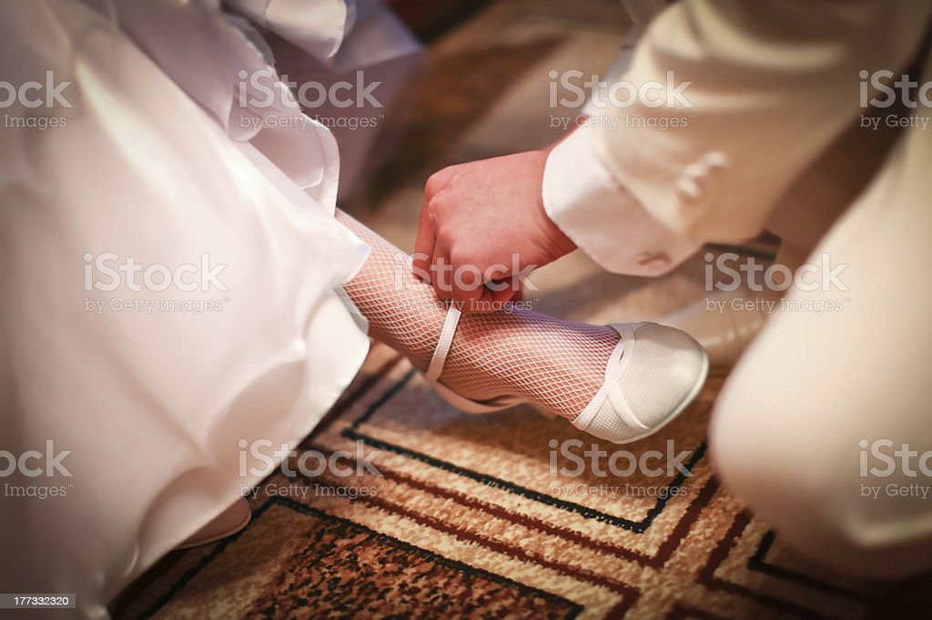 Groom is helping to wear on a bride white shoes royalty-free stock photo