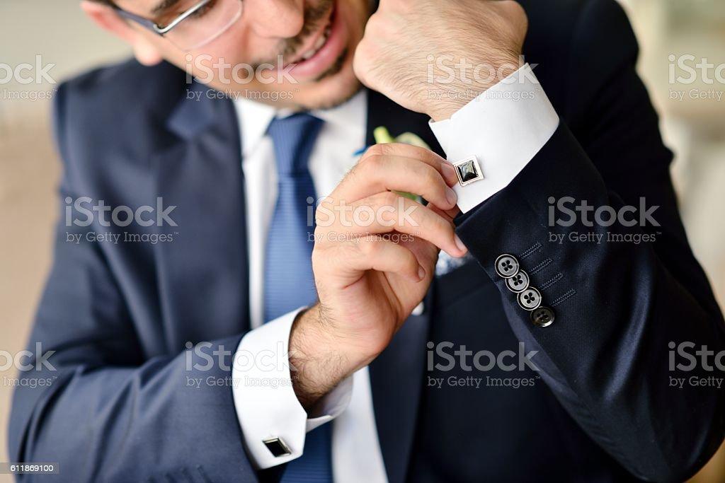 Groom is wearing cuff-links indoors stock photo