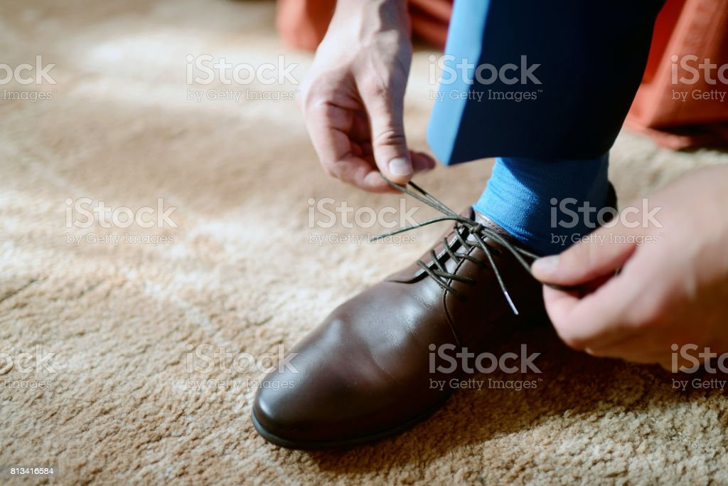 Groom is wearing shoes indoors. Male portrait of handsome guy....