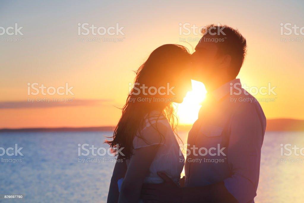 Novio besa a una novia en la frente al aire libre - foto de stock