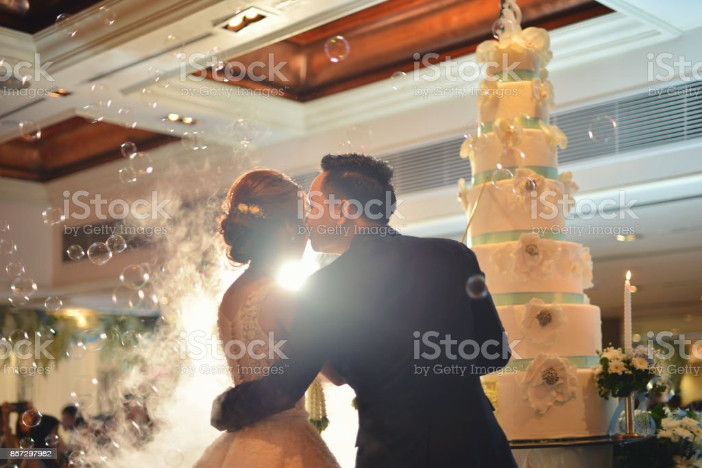 Groom kisses bride in front of cake in wedding ceremony in hall stock photo
