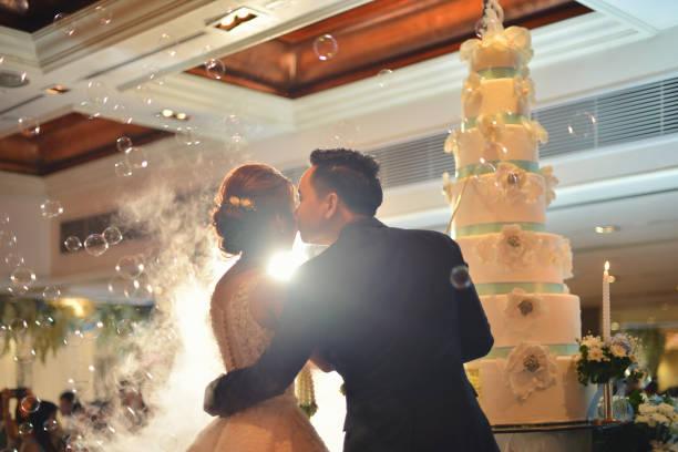bräutigam küsst braut vor kuchen in der hochzeitszeremonie in halle - make up torte stock-fotos und bilder