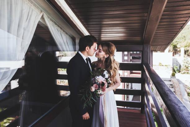 bräutigam küsst braut auf dem balkon der villa. stilvolle pärchen - hipster braut stock-fotos und bilder