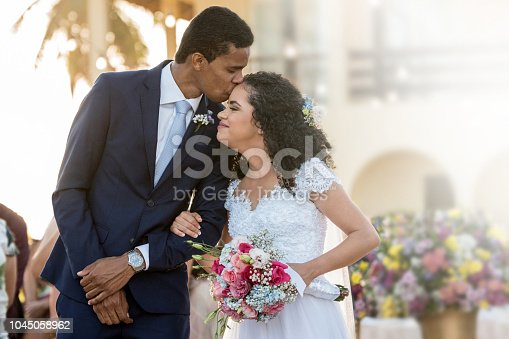 istock Groom kisses his bride on the forehead 1045058962