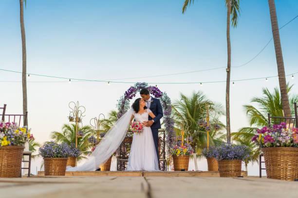 bräutigam küsst die stirn seiner braut - hochzeitsfrisur twilight stock-fotos und bilder