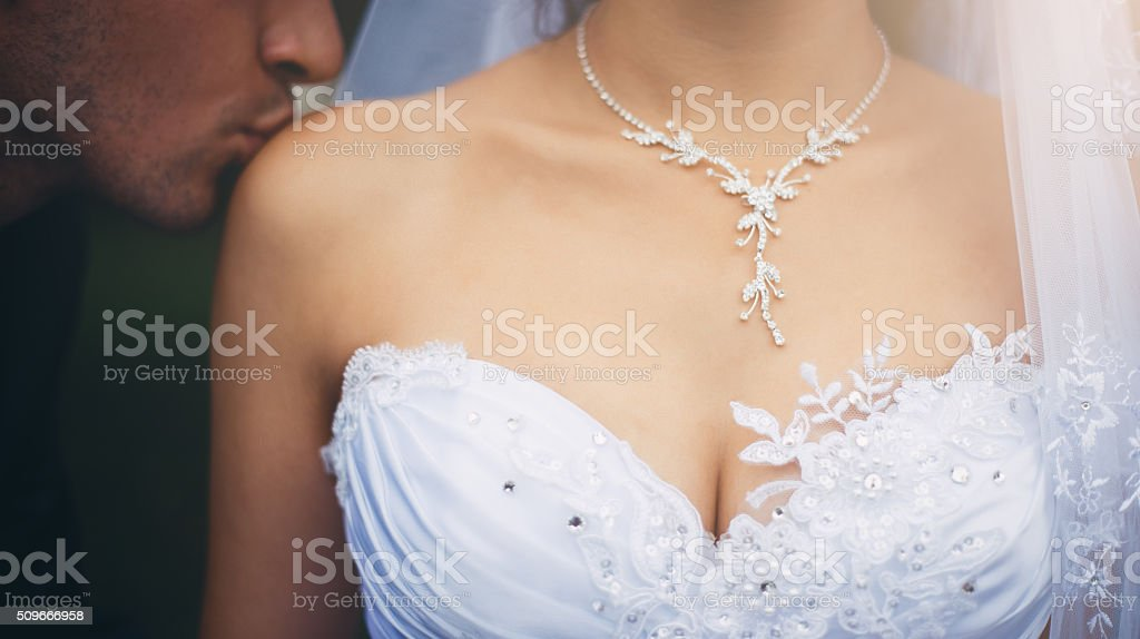Groom kissing a bride and bride's decollete stock photo