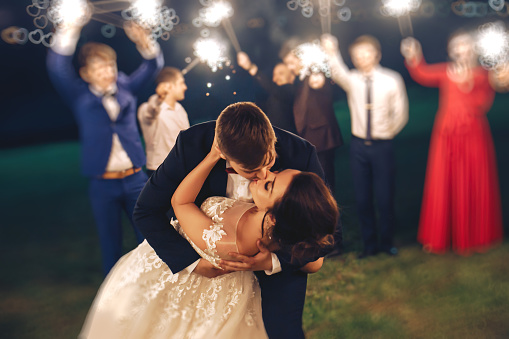 Groom kissing bride during evening wedding ceremony in nature