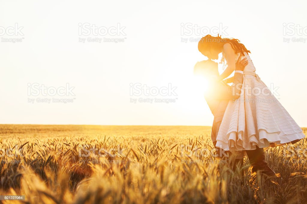 Groom lifting bride in the field of rye stock photo