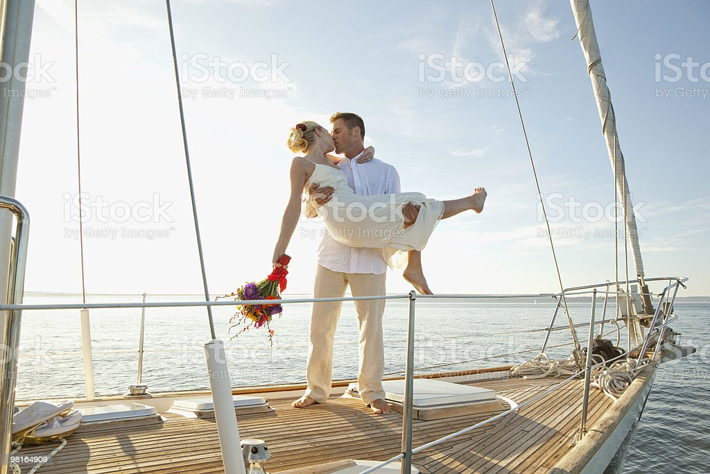 Groom lifting bride up, kissing, on sailboat royalty-free stock photo
