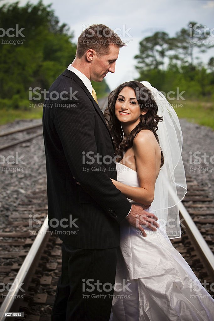 Groom looking at beautiful bride on railroad track stock photo
