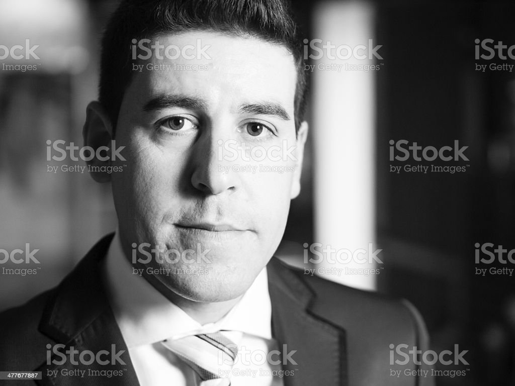 Groom looking at camera in black and white stock photo