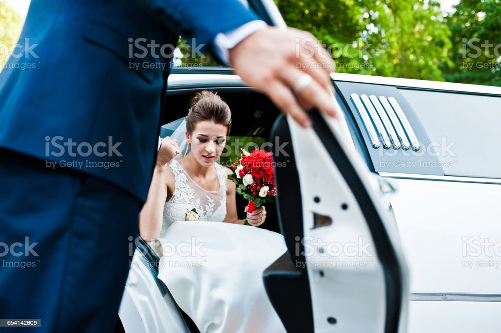 Groom open door of limousine and take hand to bride stock photo