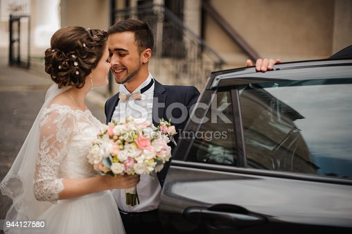 groom in a stylish black suit with a boutonniere opens the door of the wedding car, smiling and intending to kiss the bride