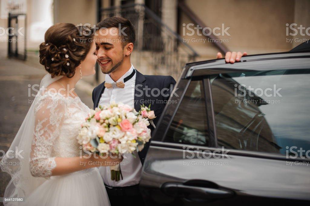 Bräutigam öffnet die Tür für das Hochzeitsauto, beabsichtigen die Braut küssen – Foto