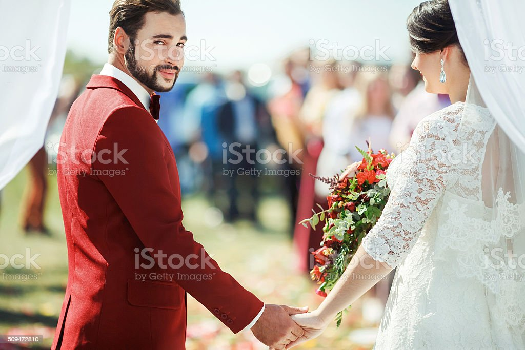 Groom pointedly looking at camera while standing in wedding ceremony stock photo