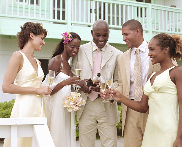 Groom pouring champagne for bride, bridesmaids and best man, smiling stock photo