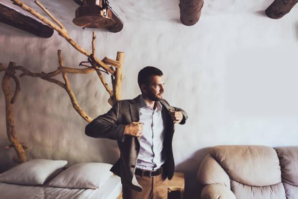 bräutigam der hochzeit vorbereiten und jacke tragen. casual-style - bräutigam anzug vintage stock-fotos und bilder