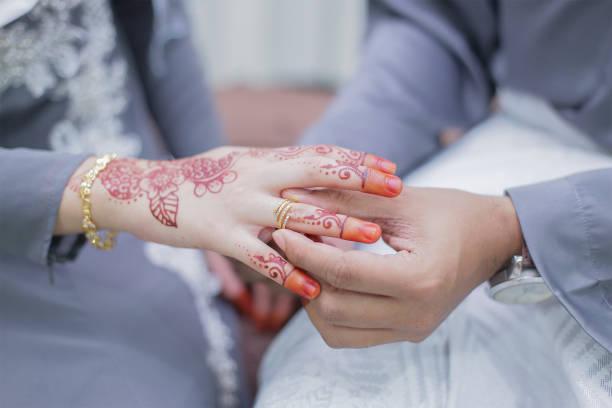 marié à mettre une bague de mariage sur la main de la mariée - mariage musulman photos et images de collection