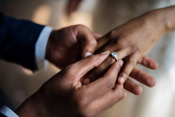 brudgummen sätter på bröllop ring bruden hand - förlovningsring bildbanksfoton och bilder