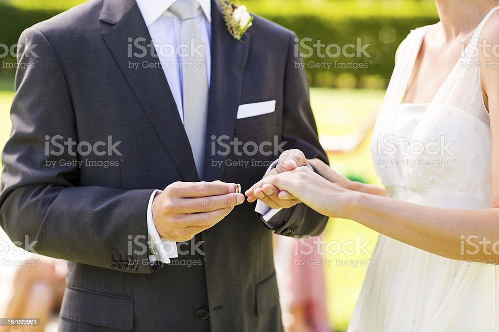 Groom Putting Ring On Bride's Finger During Garden Wedding royalty-free stock photo