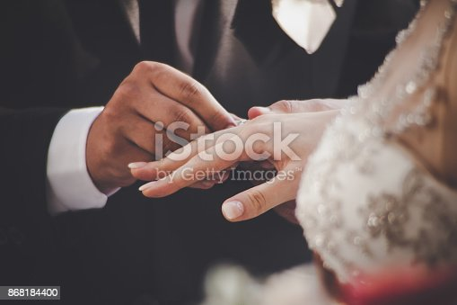 Groom Putting Ring On Bride's Finger During Wedding Ceremony. Close up shot on hands. Retro look