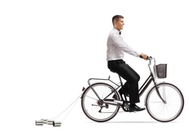 bräutigam, mit dem fahrrad mit hochzeit blechdosen hinter - zinn hochzeit stock-fotos und bilder