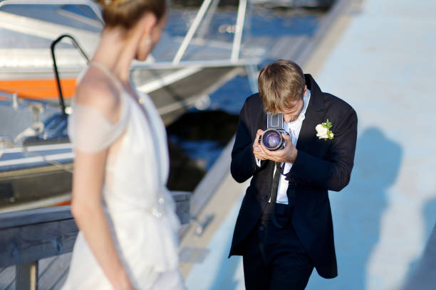 groom shooting his bride with an old camera - wedding photography and videography stock-fotos und bilder