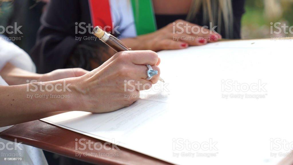 Groom signing the wedding register. stock photo