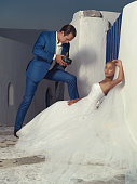 Bride posing while her groom is shooting with an old camera