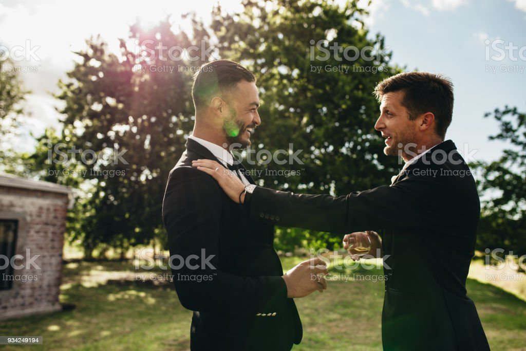 Groom talking with his best man at wedding party stock photo