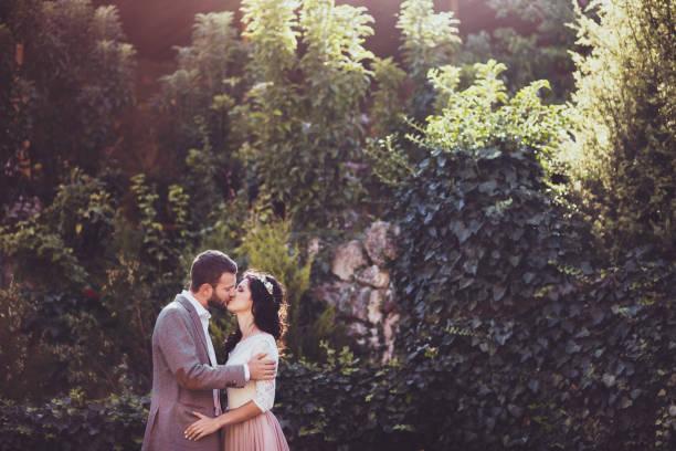 groom tenderly kissing bride surrounding by nature - hipster braut stock-fotos und bilder