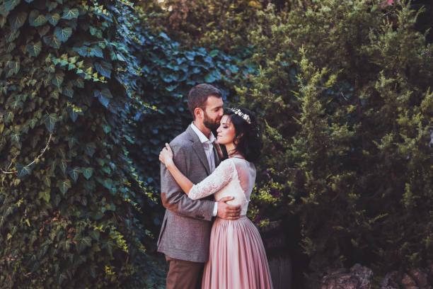bräutigam, braut, umgeben von natur zärtlich küssen - hipster braut stock-fotos und bilder