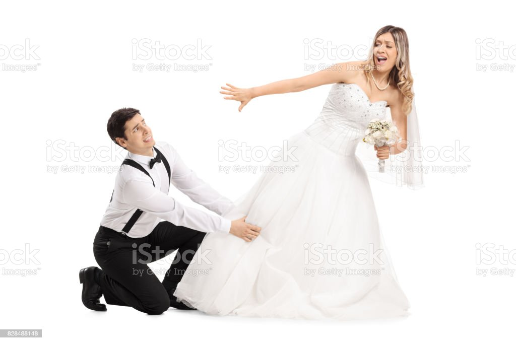 Groom trying to stop his bide from running away stock photo